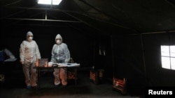 Mediocinsko osoblje u šatoru u kojem se ukazuje pomoć pacijentima za koje se sumnja da imaju Kovid-19, u Prištini 25. marta 2020. (Foto: Reuters/Laura Hasani)