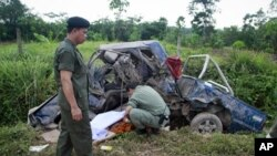 Security personnel cover the body of a Buddhist monk as they investigate the site of a bombing in the troubled southern province of Yala, May 16, 2011