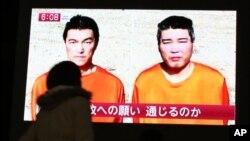 Prolaznica posmatra vesti na kojima se izveštava o dvojici Japanaca koje je otela Islamska država
