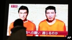 일본 동경 거리에서 인질 관련 뉴스를 보고 있는 시민 (자료사진)