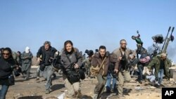 Journalists and photographers, including Hicks (R- in glasses) and Addario (far L), Moore (2nd L), Pickett (3rdL) and Poupin (4th L) run for cover during a bombing run by Libyan government planes at a checkpoint near the oil refinery of Ras Lanuf March 11