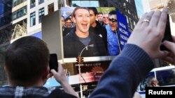 El fundador de Facebook, Mark Zuckerberg, aparece en las pantallas de Menlo Park, tras la salida a la venta de las acciones de la empresa de internet.