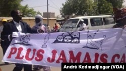 Des manifestants brandissent une banderole indiquant « Plus jamais ça » lors du sit-in des victimes des exactions perpétrées par l'ex-Direction de la documentation et de la sécurité (DDS), service des renseignements sous le régime du dictateur tchadien Hi