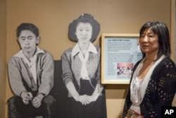 Shirley Ann Higuchi, chairman of the Heart Mountain Wyoming Foundation, stands next to a life-size photo of her parents taken in the camp.