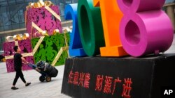 "A man pushes a cart loaded with goods past a decoration baring the words ""Business Prospers and Booming"" outside a retail and wholesale clothing mall in Beijing, China, July 9, 2018."