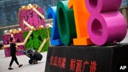 """Seorang pria mendorong gerobak barangnya melewati dekorasi yang melambangkan semangat untuk menggapai """"Kesuksesan dan Ledakan Bisnis Tahun 2018"""" di luar pusat pakaian eceran dan grosir di Beijing, China, 9 Juli 2018. (Foto: dok)."""