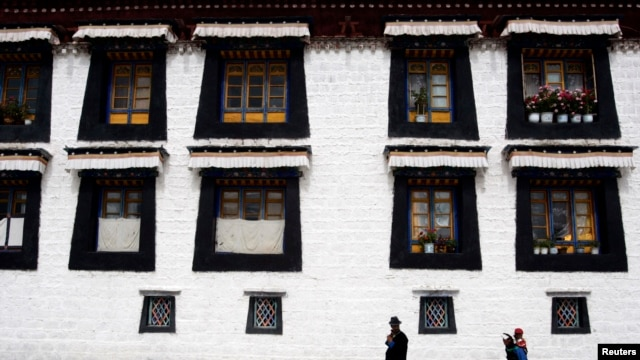 FILE - Pilgrims walk near Jokang Temple, Lhasa, Tibet Autonomous Region, China.