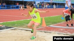 A young athlete jumps during a competition.
