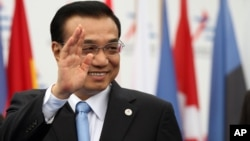 FILE - China's Premier Li Keqiang waves as he arrives at Milan's International fair for the ASEM summit of European and Asian leaders, in Milan, Italy, October 2014.
