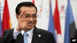 China's Premier Li Keqiang waves as he arrives to Milan's International fair for the second day of a ASEM summit of European and Asian leaders, in Milan, Italy, Friday, Oct. 17, 2014.