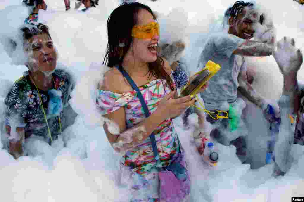 Revelers react at a foam party during Songkran Festival celebrations in Bangkok, Thailand.