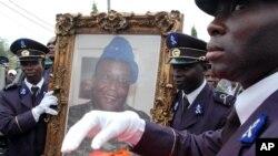 Des soldats tiennent le portrait de Robert Guéï à Abidjan, le 18 août 2006. (AP Photo)