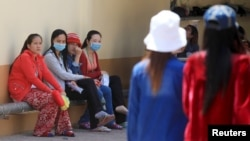 FILE - Garment workers rest inside a factory after their lunch time in Phnom Penh.