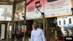 "Serge Noukoue in front of the Paris cinema airing the ""Nollywood Week"" film festival (Lisa Bryant/VOA)"