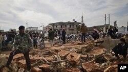 Syrians wait alongside rubble in Maaret Misreen near Idlib to buy bread at a local bakery, December 12. (AP)