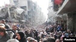 Warga mengantre untuk mendapatkan bantuan makanan dari PBB di kamp pengungsi al-Yarmouk, Damaskus selatan.