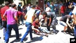 Người dân đang giúp đỡ một người bị thương sau vụ đánh bom tự sát ở Suruc, Thổ Nhĩ Kỳ, hôm 20/7/2015.