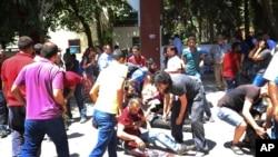 Người bị thương được giúp đỡ sau vụ nổ bom tại thành phố Suruc ở đông nam Thổ Nhĩ Kỳ, ngày 20/7/2015.