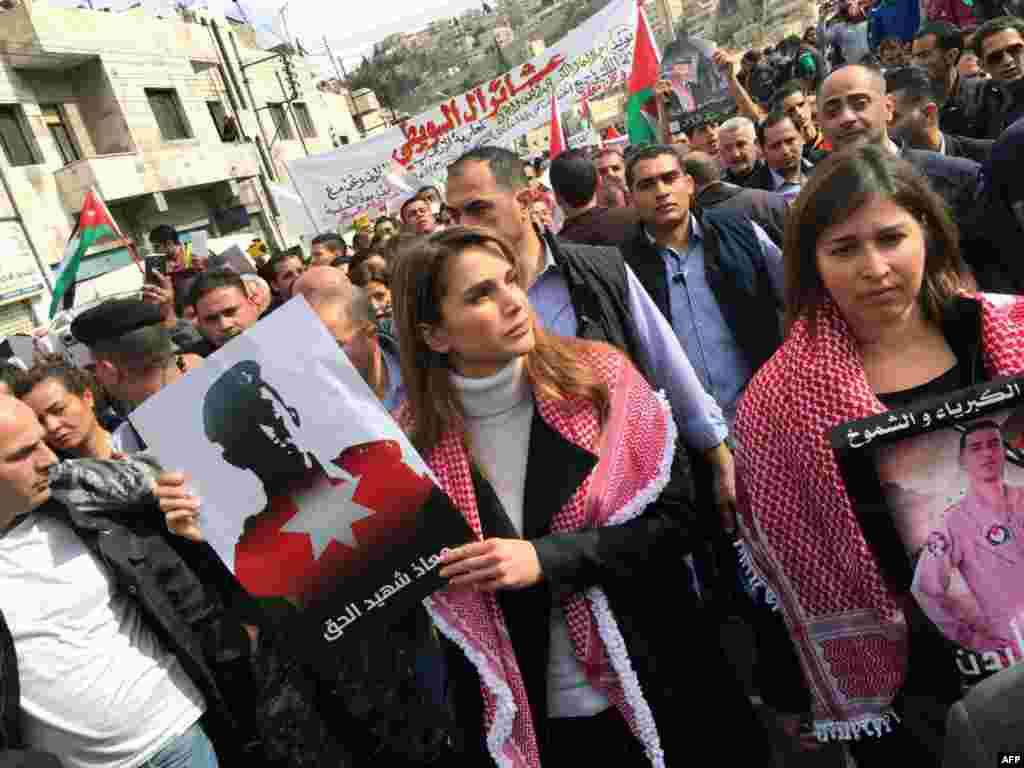 A handout picture released by the Jordanian Queen Rania's office shows her holding a placard during a demonstration in the capital Amman to express her solidarity with the pilot murdered by the Islamic State (IS) group.