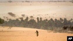 Une jeune fille à la recherche de l'eau sur les près d'un puits à Barrah, un village du désert dans la bande sahélienne du Tchad, 20 avril 2012.