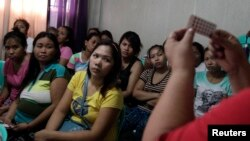 FILE - Women listen during a family planning lecture by a Likhaan NGO health worker at a reproductive health clinic in Tondo, metro Manila, Philippines, Jan. 12, 2016.