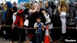 Migrants line up to receive personal hygiene goods distributed by the U.N. High Commissioner for Refugees, outside the main building of the disused Hellenikon airport where stranded refugees and migrants, most of them Afghans, are temporarily accommodated