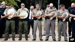 Law enforcement officers from Texas bow their heads in prayer during a service Monday, July 11, 2016, at T.B. Butler Plaza in Tyler, Texas. Residents joined officers from several agencies in remembering the four Dallas police officers and one Dallas Area Rapid Transit officer who died July 7, 2016. (Andrew D. Brosig/Tyler Morning Telegraph via AP)