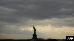 FILE - Cloudy skies hang over the The Statue of Liberty as seem from the Staten Island Ferry near New York City, US, on Dec. 17, 2018.