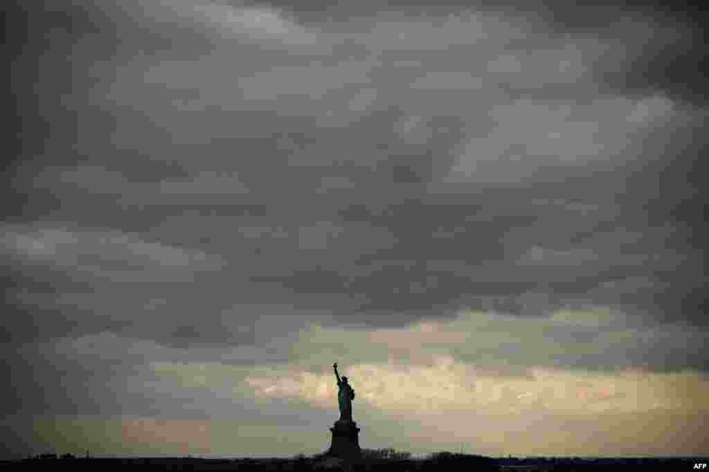 Cloudy skies hang over the The Statue of Liberty as seem from the Staten Island Ferry near New York City, US.
