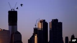 Dos pájaros vuelan a la salida del sol, con el fondo de la Torre Uno del Centro de Comercio Mundial, que podría convertirse en el edificio más alto de EE.UU., este lunes 30 de abril de 2012.