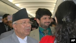 Prime Minister Madhav Kumar Nepal (L) greets fellow passengers aboard a commercial flight from Bhutan to Kathmandu, 30 Apr 2010