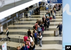 FILE - A long line of travelers wait for the TSA security check point at O'Hare International airport, in Chicago.