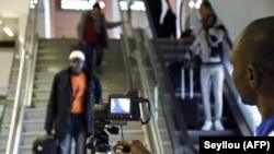 Des agents de santé contrôlent les passagers à l'arrivée avec un scanner thermique à l'aéroport international Blaise Diagne de Dakar, le 30 janvier 2020. (Seyllou / AFP)
