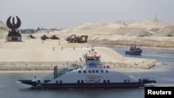 The ship 'Long Life Egypt' crosses a new section of the Suez Canal in Ismailia, Egypt, Aug. 6, 2015. The canal was extended in hopes of powering an economic turnaround. But toll revenues have fallen in September, dampening hopes that a new parallel waterway will boost the economy in the immediate future.