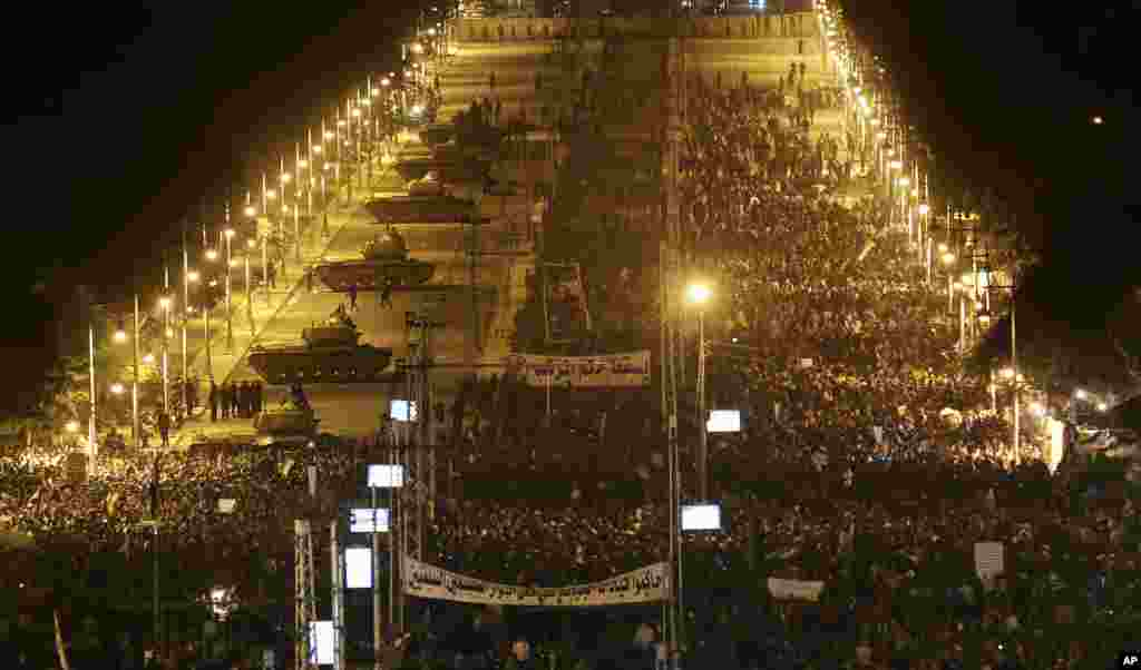 Army tanks, left, deploy as Egyptian protesters gather outside the presidential palace during a demonstration against President Mohamed Morsi in Cairo, Egypt, December 11, 2012.