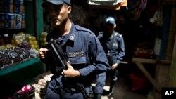 FILE - Honduras National Police officers patrol in El Mayoreo market in Tegucigalpa, Honduras, June 1, 2013.