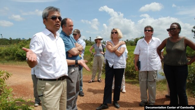 Youk Chhang, Elizabeth Becker and Michael ABRAMOWITZ, USHMM Director and his delegations at a B52 bomb pond near the Chinese airport, Kampong Chhnang province. Oct 24, 2012. Photo by Nhean Socheat.