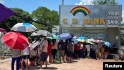 FILE - People line up outside a bank to withdraw cash, in Yangon, Myanmar, May 13, 2021.