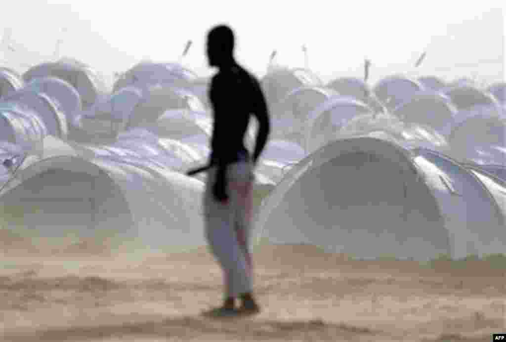 Displaced people play soccer backdropped by their refugee camp at the Tunisia-Libyan border. The camp houses about 5,000 people, trying to handle the large numbers of expatriates crossing the border into Tunisia. (AP/Lefteris Pitarakis)