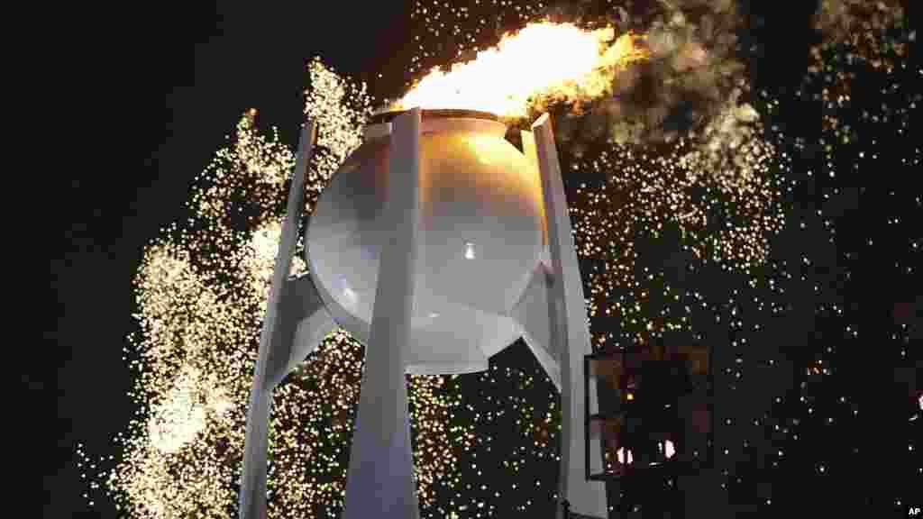 Des feux d'artifice explosent au-dessus de la flamme olympique lors de la cérémonie d'ouverture des JO d'hiver de 2018 à Pyeongchang, en Corée du Sud, le 9 février 2018.