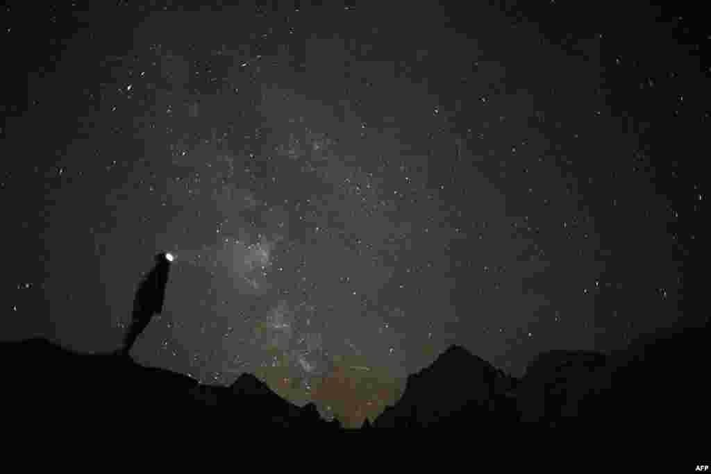 Seorang fotografer bersiap mengambil foto hujan meteor Perseid tahunan di desa Crissolo, dekat Cuneo, di kawasan pegunungan Monviso di Italia utara. Hujan meteor Perseid berlangsung setiap tahun saat Bumi melewati awan puing sisa Komet Swift-Tuttle.