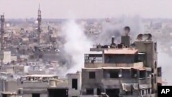 This image made from amateur video purports to show smoke rising from buildings in Homs, Syria. Syrian forces renewed shelling of the central city of Homs on Monday, one day after the head of the U.N. observers' mission demanded that warring parties allow