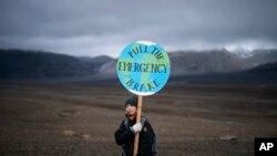 Seorang gadis memegang papan bertuliskan 'pull the emergency brake' ketika ia menghadiri upacara di daerah yang dulunya adalah gletser Okjokull, di Islandia, Minggu, 18 Agustus 2019. (Foto: AP)