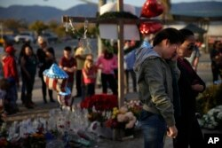 Yanira Perez (2-R) wipes her eyes as she and her mother, Marcela, pay respects at a makeshift memorial to honor the victims of Wednesday's shooting rampage, Dec. 5, 2015, in San Bernardino, California.