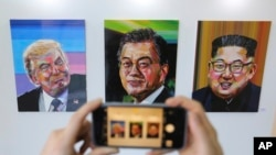 A visitor takes a photograph of images, from left, of U.S. President Donald Trump, South Korean President Moon Jae-in and North Korean leader Kim Jong Un during an exhibition at an annex of the presidential Blue House in Seoul, South Korea, Jan. 3, 2019.