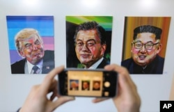 FILE - A visitor takes images, from left, of U.S. President Donald Trump, South Korean President Moon Jae-in and North Korean leader Kim Jong Un during an exhibition at an annex of the presidential Blue House in Seoul, South Korea, Jan. 3, 2019.