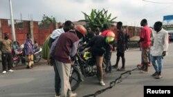 Les gens regardent une fissure sur la route causée par des tremblements de terre comme des répliques après l'éruption du volcan du mont Nyiragongo près de Goma, en République démocratique du Congo, le 26 mai 2021.