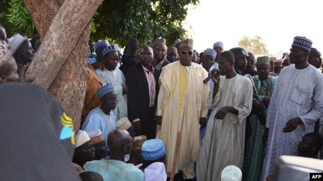 A villager speaks standing next to the governor of Borno State, Kashim Shettima (C), during Shettima's visit to Benisheik, on September 19, 2013, after a violent attack by Boko Haram Islamists kills at least 87 people.