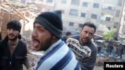 30일 시리아 다마스쿠스 인근 번화가에 정부군의 미사일 공격이 있은 후 사람들이 시체를 옮기고 있다.