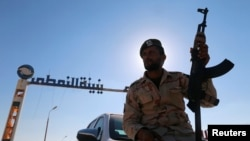 FILE - A member of Libyan forces loyal to eastern commander Khalifa Haftar holds a weapon as he sits on a car in front of the gate at Zueitina oil terminal in Zueitina, west of Benghazi, Libya, Sept. 14, 2016.